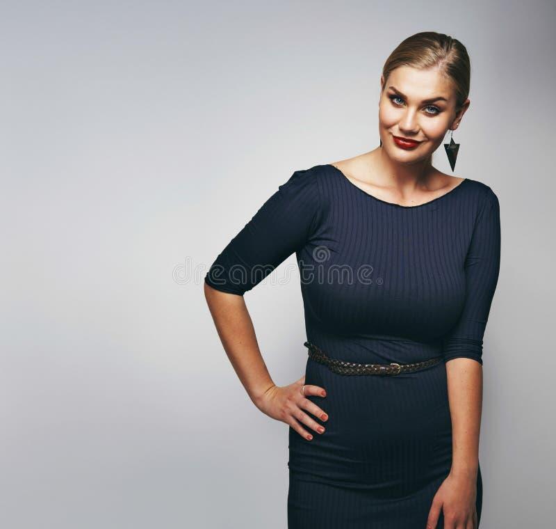 Señora joven magnífica que presenta en vestido negro fotos de archivo libres de regalías