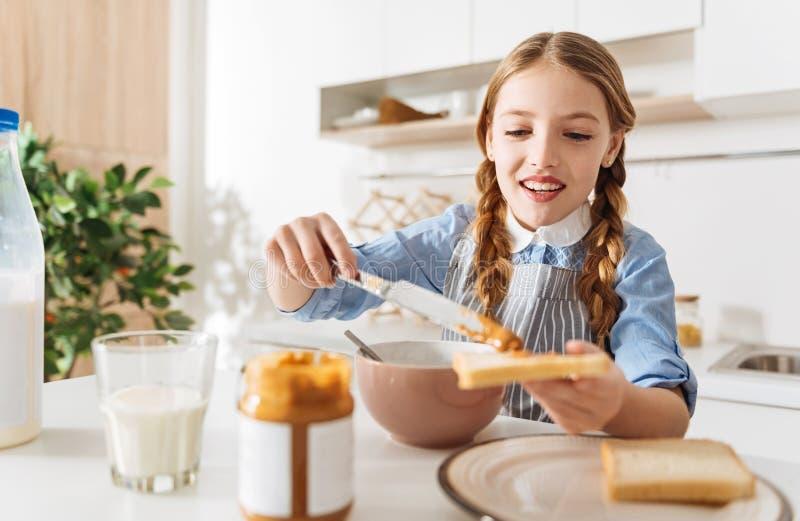 Señora joven magnífica que se hace que desayuna imagen de archivo