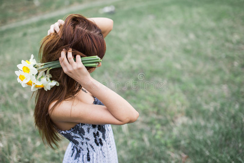 Señora joven pelirroja que sostiene el ramo de narcisos foto de archivo libre de regalías