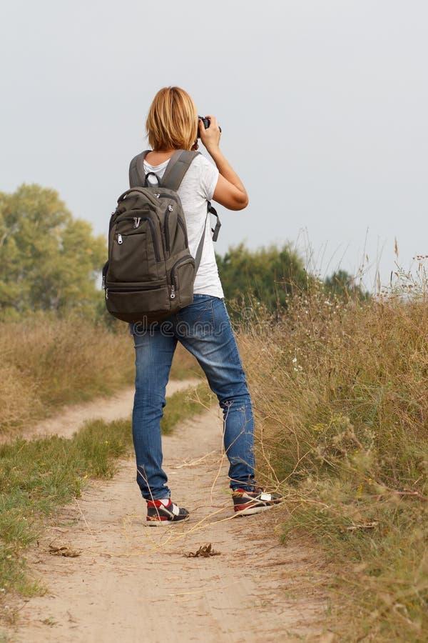 Señora joven que camina en un camino rural con la cámara digital imagen de archivo
