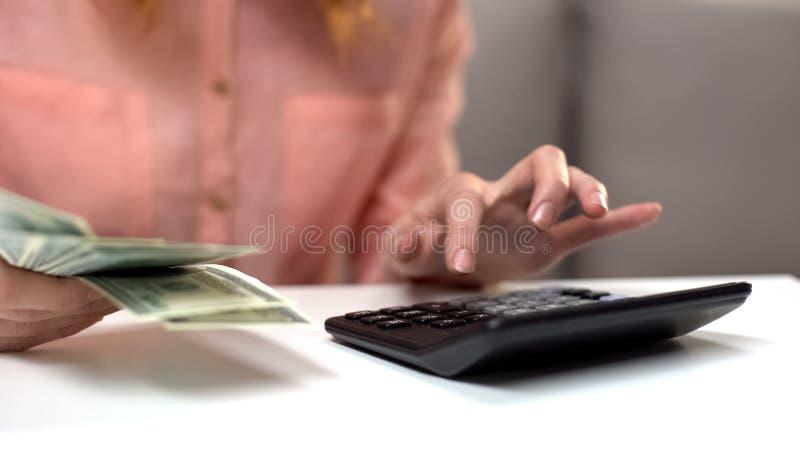 Señora joven que cuenta costos usando la calculadora, llevando a cabo dólares a disposición, renta imagenes de archivo