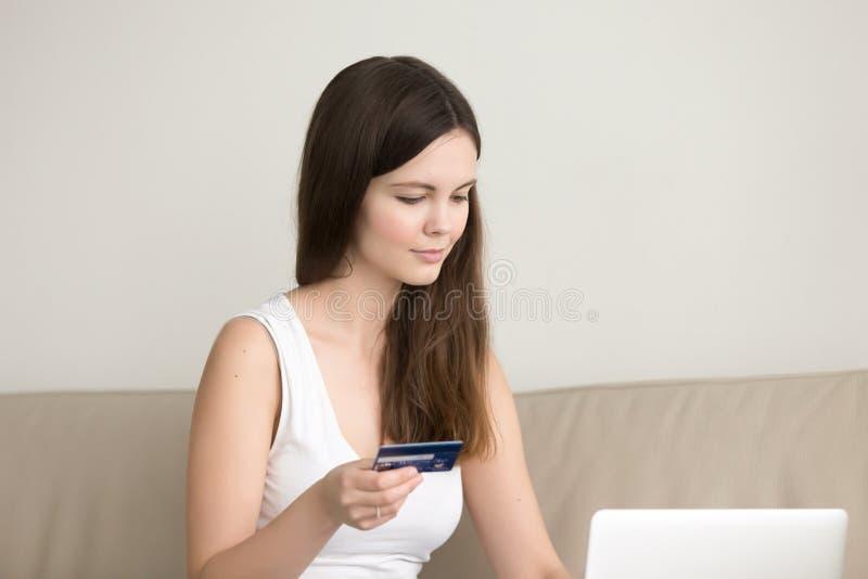 Señora joven que hace compras en línea en casa, pagando por la tarjeta de crédito foto de archivo
