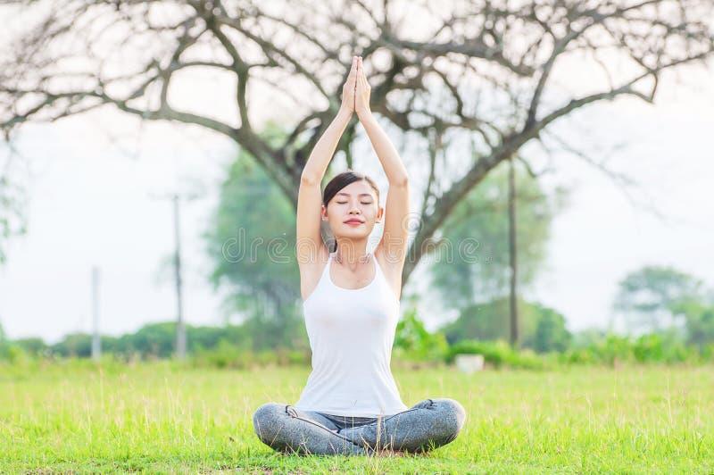 Señora joven que hace ejercicio de la yoga en el área al aire libre del campo verde que muestra la calma pacífica en mente de la  foto de archivo libre de regalías