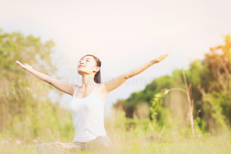 Señora joven que hace ejercicio de la yoga en el área al aire libre del campo verde que muestra la calma pacífica en mente de la  fotografía de archivo
