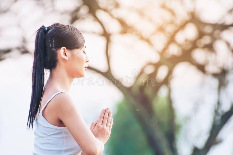 Señora joven que hace el ejercicio de la yoga al aire libre imagen de archivo libre de regalías