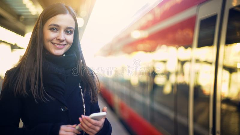 Señora joven que mecanografía en smartphone en la plataforma cerca del tren y que sonríe a la cámara imagenes de archivo