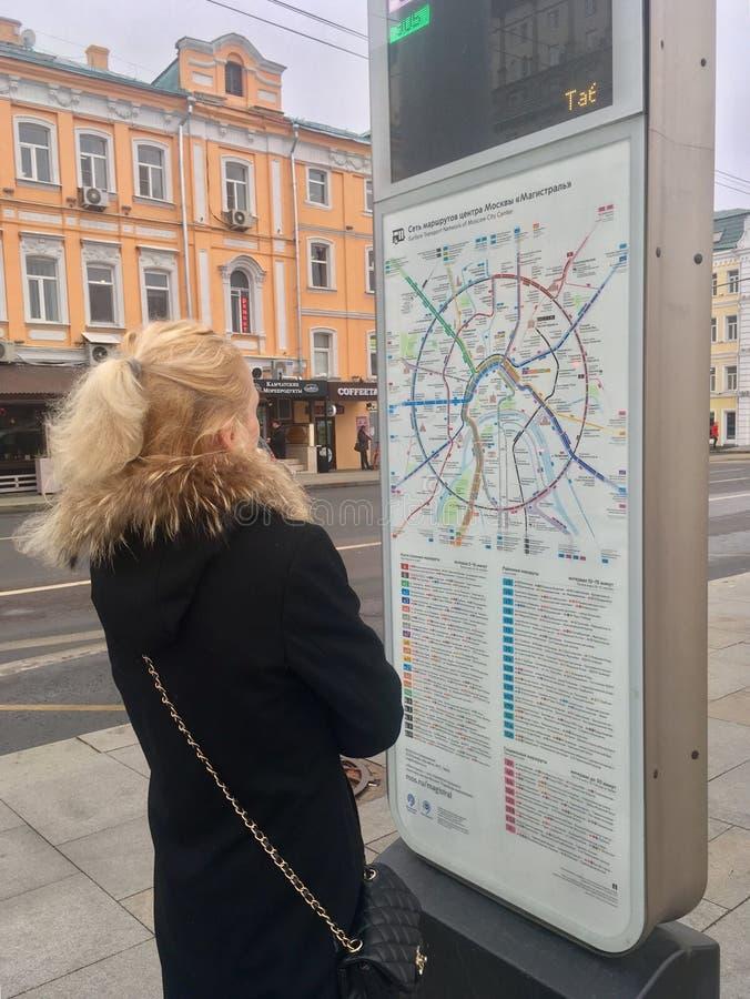 Señora joven que mira el mapa del transporte imagen de archivo
