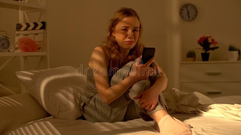 Señora joven que se sienta en cama y que llora, sosteniendo el teléfono en las manos, recibiendo malas noticias foto de archivo
