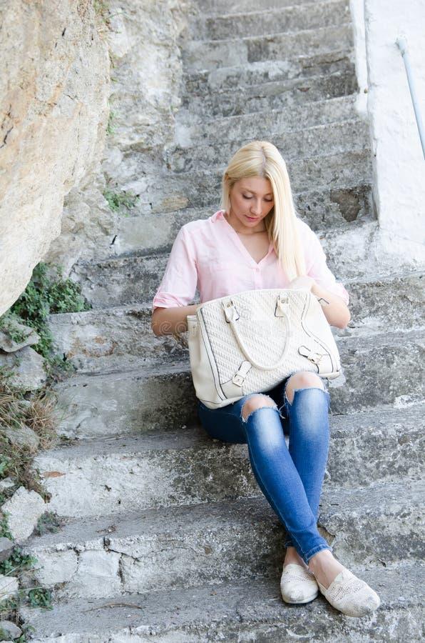 Señora joven que se sienta en las escaleras del cemento imagenes de archivo