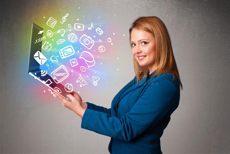 Señora joven que sostiene el cuaderno con multimedias dibujadas mano colorida imagen de archivo