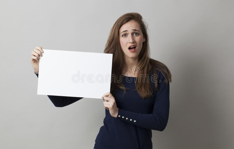 Señora joven que sostiene el tablero o el papel en blanco para un anuncio publicitario fotos de archivo