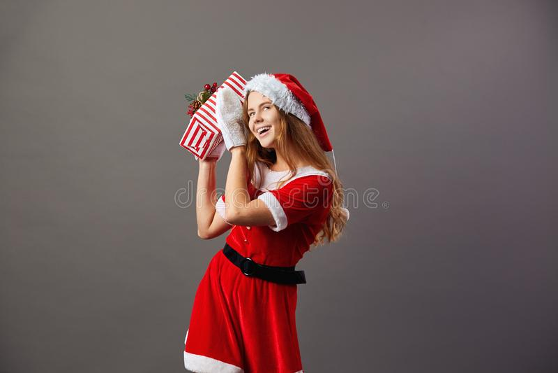 Señora joven y hermosa Claus se vistió en el traje rojo, el sombrero de Papá Noel y los guantes blancos sostienen el regalo de la fotos de archivo libres de regalías