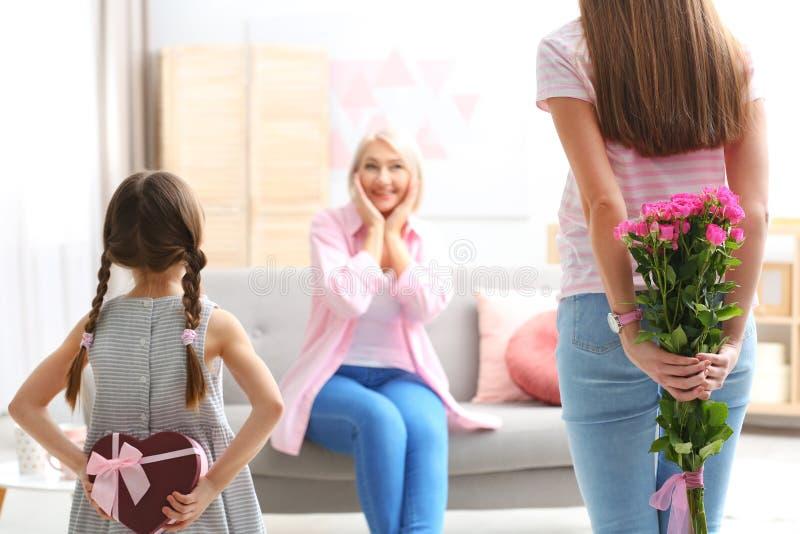 Señora joven y su hija que felicitan a la abuela foto de archivo libre de regalías