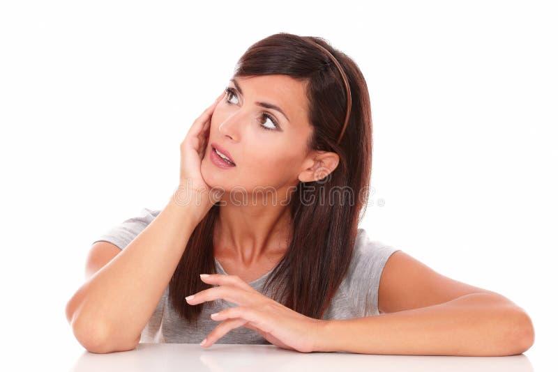 Señora latina que se pregunta mientras que mira a su derecha para arriba foto de archivo libre de regalías
