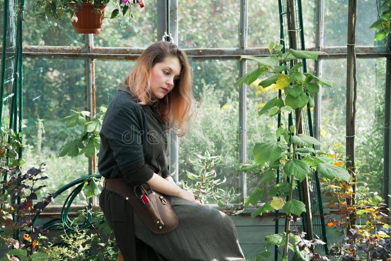 Señora linda joven que trabaja en el invernadero fotografía de archivo