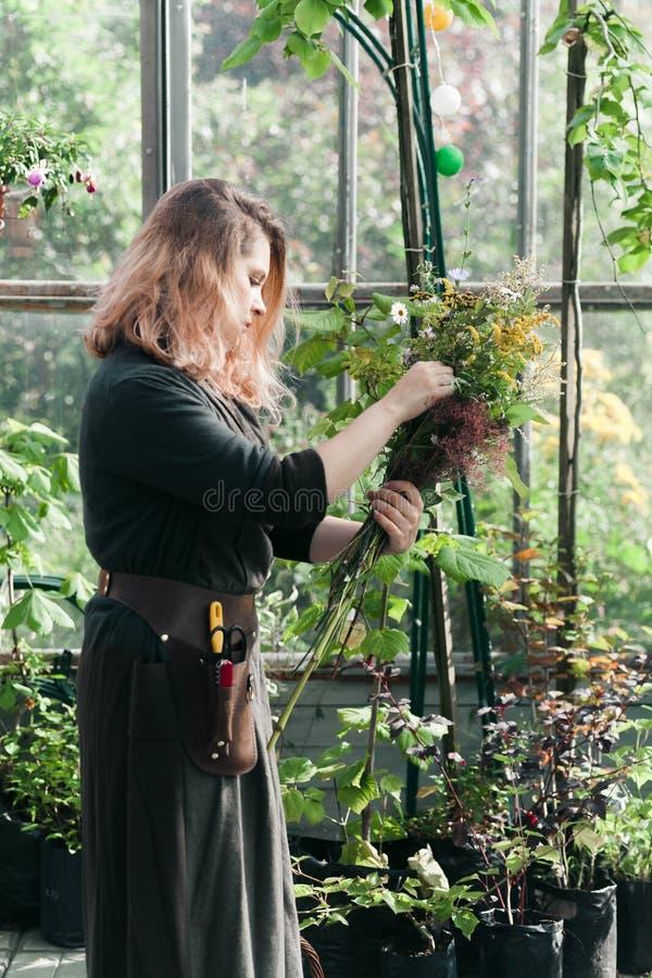 Señora linda joven que trabaja en el invernadero imágenes de archivo libres de regalías