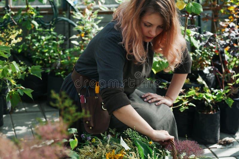 Señora linda joven que trabaja en el invernadero imagenes de archivo