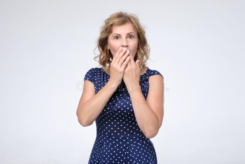 Señora madura caucásica en el vestido azul que cubre su boca con las palmas fotos de archivo libres de regalías