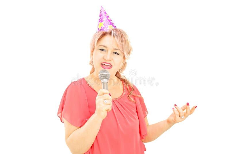 Señora madura con el sombrero del partido que canta en el micrófono imagen de archivo