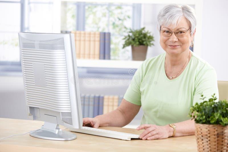 Señora madura con la sonrisa del ordenador fotografía de archivo