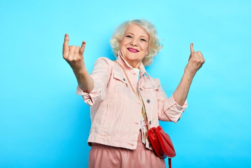 Señora magnífica positiva alegre de la anciano que hace la muestra de la roca foto de archivo