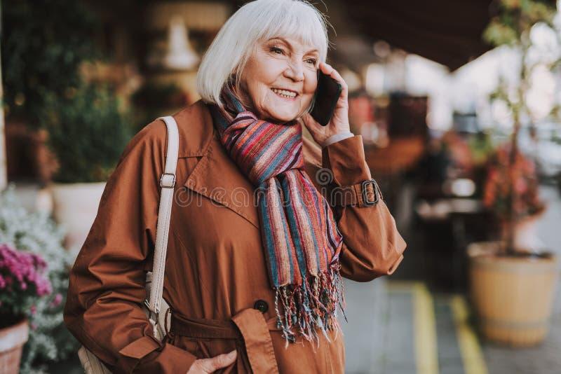 Señora mayor alegre con la mochila que habla en el teléfono móvil en la calle imagen de archivo libre de regalías