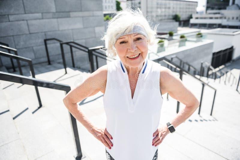 Señora mayor alegre que ejercita en la escalera grande de la ciudad al aire libre imágenes de archivo libres de regalías