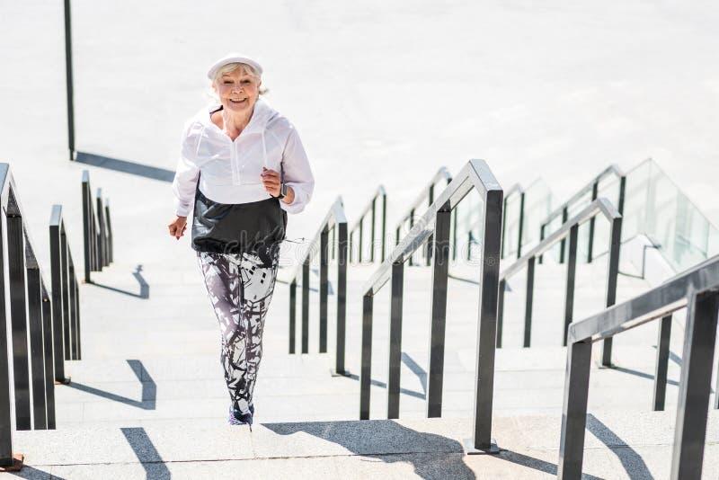 Señora mayor alegre que funciona con para arriba pasos concretos al aire libre imagenes de archivo