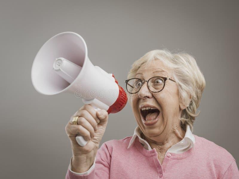 Señora mayor alegre que grita en un megáfono foto de archivo libre de regalías