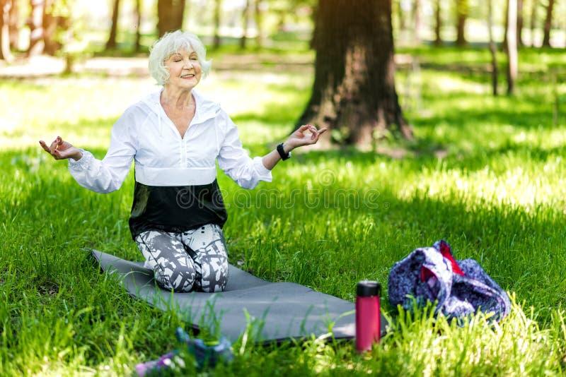 Señora mayor alegre que hace ejercicios de la relajación en bosque imágenes de archivo libres de regalías