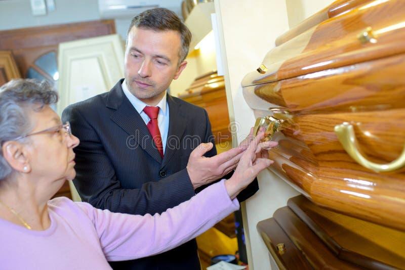 Señora mayor con el director de funeraria que elige el ataúd foto de archivo