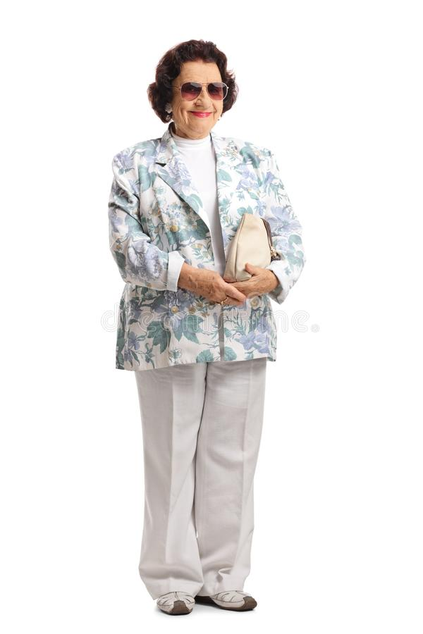 Señora mayor con gafas de sol y una sonrisa del monedero fotos de archivo