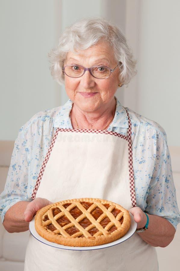 Señora mayor con la torta hecha en casa fotografía de archivo