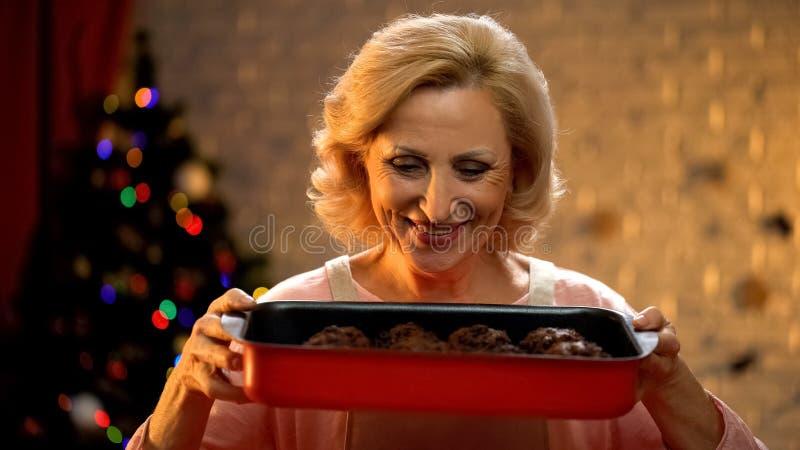 Señora mayor con los molletes tradicionales del chocolate de Navidad, familia que espera para la víspera fotografía de archivo libre de regalías