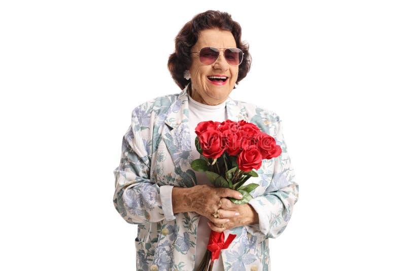 Señora mayor con un manojo de risa de las rosas fotografía de archivo