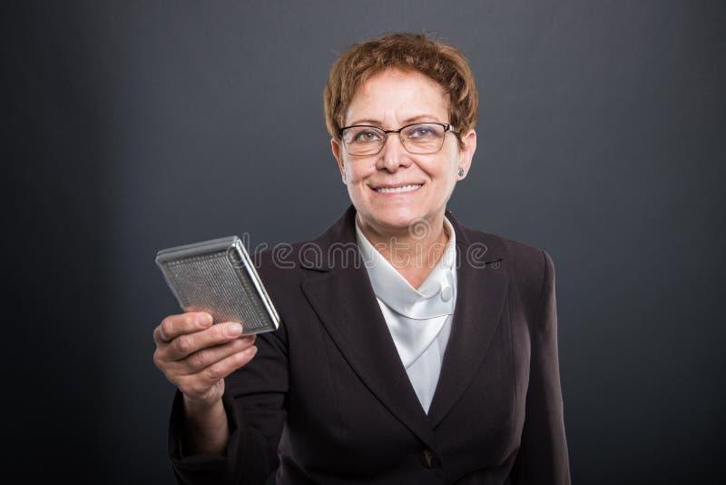 Señora mayor del negocio que celebra la caja y la sonrisa del cigarrillo fotos de archivo