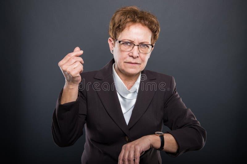 Señora mayor del negocio que muestra el tiempo es oro gesto fotografía de archivo