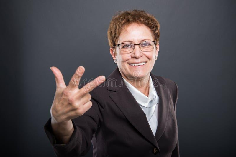 Señora mayor del negocio que muestra gesto del número tres fotos de archivo
