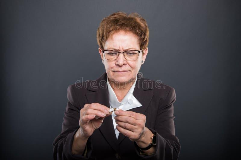 Señora mayor del negocio que rompe un cigarrete foto de archivo