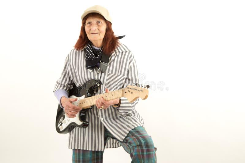 Señora mayor divertida que toca la guitarra eléctrica foto de archivo