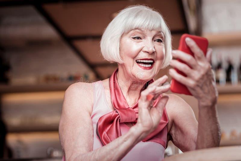 Señora mayor elegante hermosa con corte de pelo corto que comprueba medios sociales foto de archivo libre de regalías
