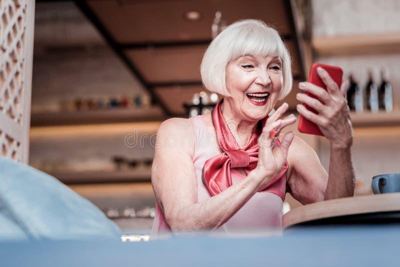 Señora mayor emocionada con corte de pelo de la sacudida observando el mensaje recibido fotos de archivo libres de regalías