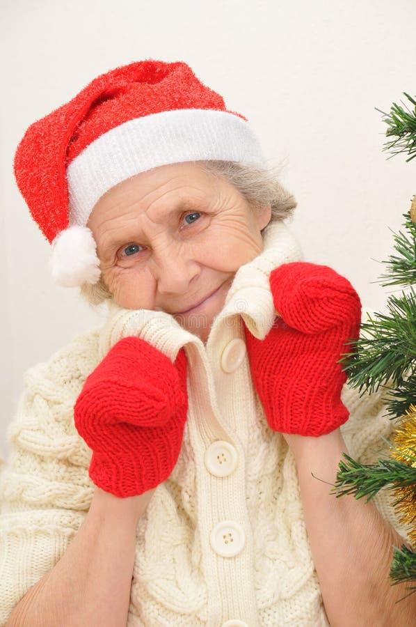 Señora mayor en el sombrero rojo de Papá Noel y manoplas rojas fotos de archivo