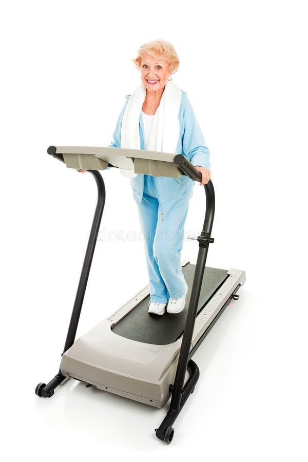 Señora mayor en la rueda de ardilla fotografía de archivo