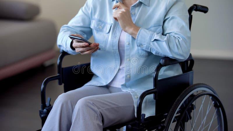 Señora mayor en silla de ruedas que charla en el smartphone, tecnologías modernas, artilugio foto de archivo libre de regalías