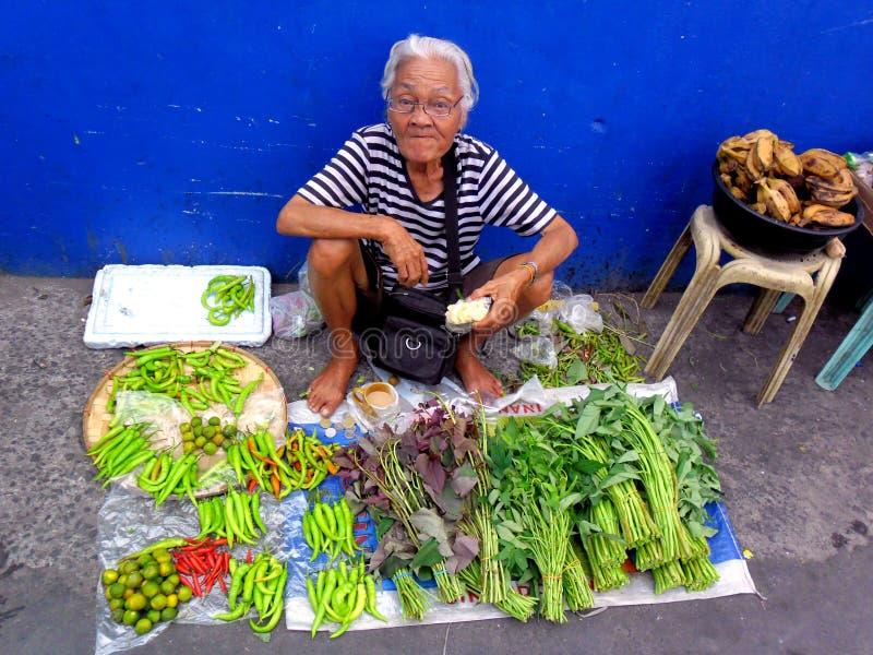 Señora mayor en un mercado en el cainta, rizal, Filipinas que venden las frutas y verduras fotos de archivo