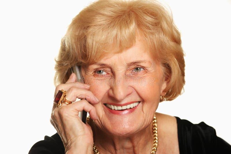 Señora mayor feliz que habla en el teléfono imagen de archivo