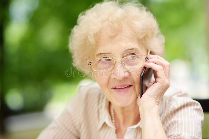 Señora mayor hermosa con el pelo blanco rizado que habla en el teléfono Comunicación, charla, chisme Formas de vida mayores de la imágenes de archivo libres de regalías