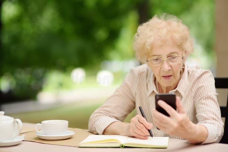 Señora mayor hermosa con el pelo blanco rizado que trabaja en café o restaurante del aire libre imagenes de archivo