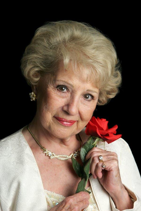 Señora mayor hermosa con Rose imagen de archivo libre de regalías